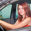 Stock Photo: Young woman is driving a car