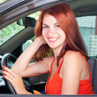 Young woman is driving a car - Stock Photo
