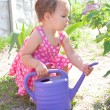 Little baby watering flowers — Stockfoto