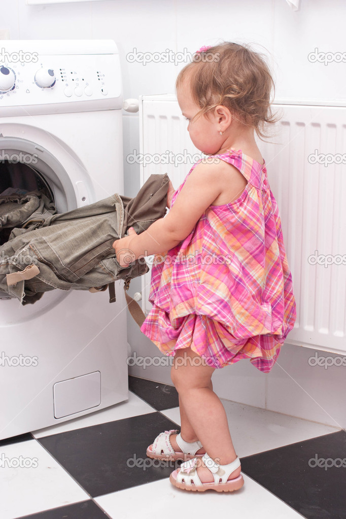Little baby reaching for the washed things out of the washing machine — Stockfoto #10033461