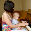 Baby play the piano - Stock Photo