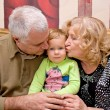 Stock Photo: Grandparents kissing baby