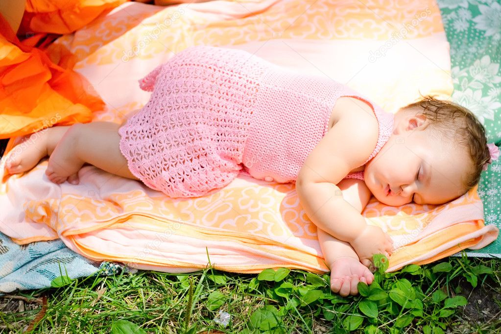 Cute baby girl sleeping with her hands under her face in the open air — Stock Photo #9928544