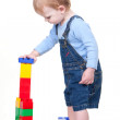 Small child building tower from cubes - Stock Photo
