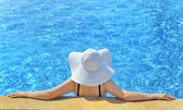 Woman with hat relaxing on swimming pool — Stock Photo