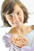 Girl holding pills — Stock Photo