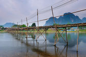 Wood bridge over river song to riverside guesthouse, Vang vieng, — Stock Photo