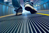 Foot walking in airport escalator perspective view (ground level) — Stock Photo