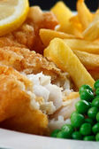 Close up of fish and chips with peas and a slice of lemon. — Stock Photo