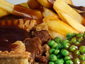 Close up of Steak Pie and chips with peas and gravy. — Stock Photo