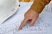 Mänsklig hand pekar på planer — Stockfoto