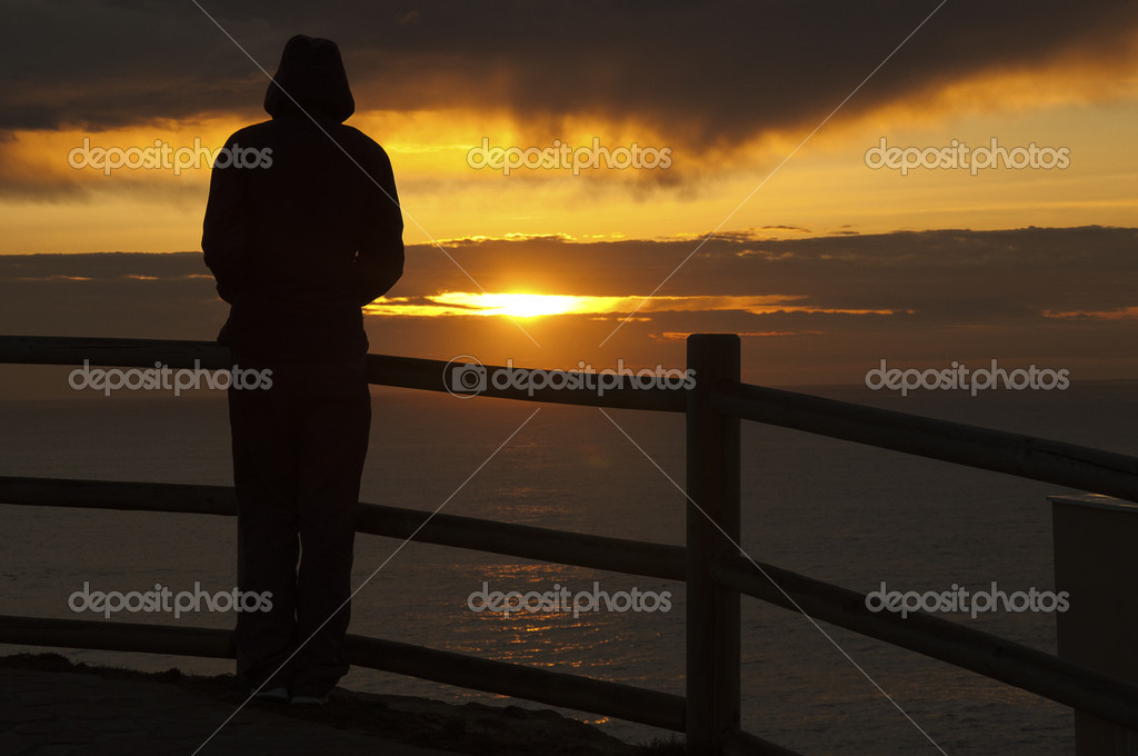 A silhouette on a sunset with a fence and the sea  Stock Photo #10224026