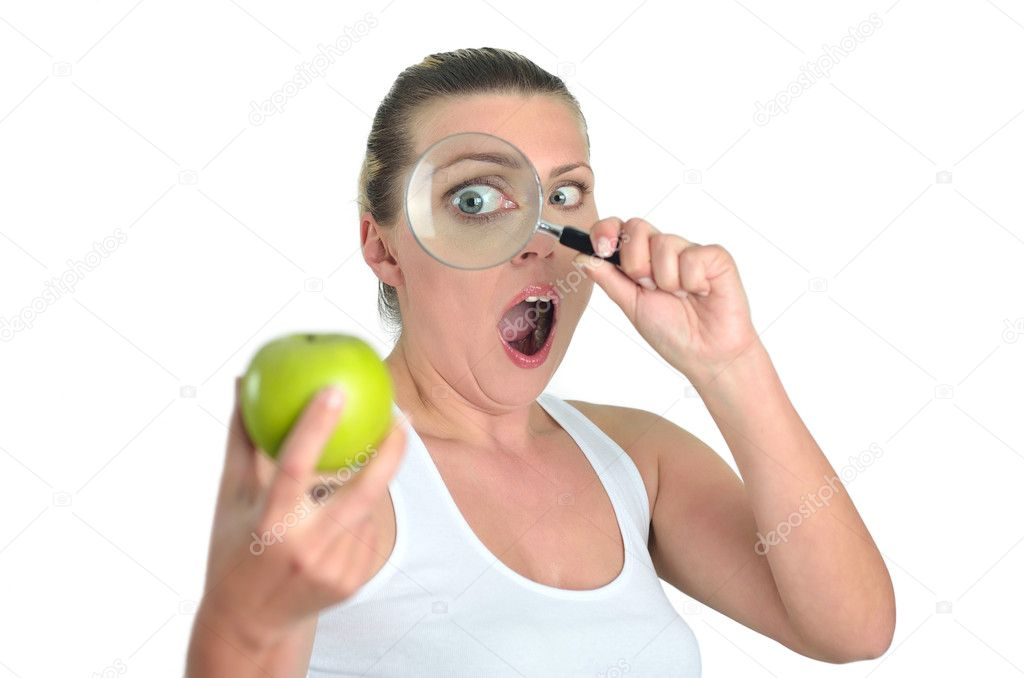 Woman watching green apple with a magnifying glass — Stock Photo #10071710