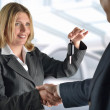 Businesswoman giving keys to businessman — Stock Photo
