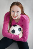 Attractive blond girl holding a soccer ball and sitting on floor — Stock Photo