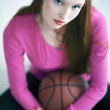 Beautiful long haired girl holding a basket ball and sitting — Stock Photo