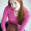 Beautiful long haired girl holding a basket ball and sitting — Stock fotografie