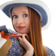 Stock Photo: Long haired female holding paper-bags and wear a hat