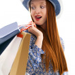 Long haired female holding paper-bags and wear a hat — Stock Photo