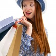 Long haired female holding paper-bags and wear a hat — Stock Photo #10468144