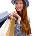 pelo largo mujer sosteniendo bolsas de papel y usar un sombrero — Foto de Stock   #10468193