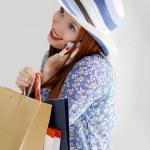 joven hermosa mujer sosteniendo bolsas de papel y hablando celular — Foto de Stock   #10468340