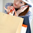 Young beautiful female holding paper-bags and talking cellphone — Stock Photo #10468384