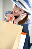 Young beautiful female holding paper-bags and talking cellphone — Stock Photo