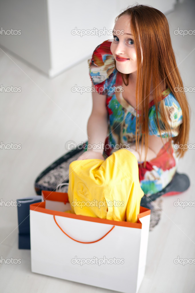 Long haired happy girl holding and looking dresses with shopping packs sitting on floor — Stock Photo #10468680