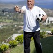 Stock Photo: Retired football player with walking stick holding soccerball