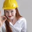 Long haired happy girl with yellow helmet showing the okey sign — Stock Photo #10643194