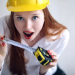 Stock Photo: Girl holding tape measure and wearing safety hat