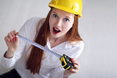 Woman holding a tape measure and wearing a safety hat — Stock Photo