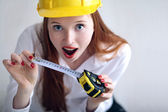 Girl holding a tape measure and wearing a safety hat — Stock Photo