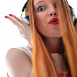 Long haired red headed girl with headphones listening to music — Stock Photo