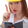 Young beautiful female with yellow helmet using a cellphone — Stock Photo