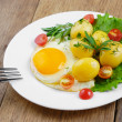 Fried egg with potato - Stock Photo