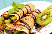 Kiwi crepes with chocolate syrup — Stock Photo