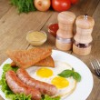 Fried eggs with sausages - Stock Photo