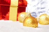 Gift box and yellow christmas balls — Stock Photo