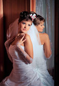 Bride standing next to the mirror — Stock Photo
