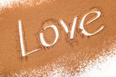 "The word ""love"" written in Cocoa scattered — Stock Photo"
