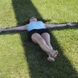 Young woman laying over cross shadow in the grass — Stock Photo