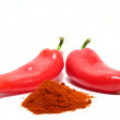 Red paprikas and ground paprika — Stock Photo