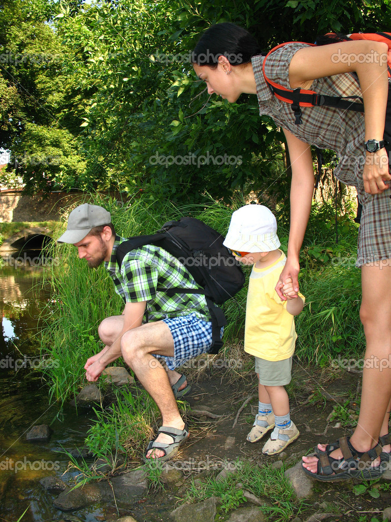 Young family on trip by the river. Mother and son hand in hand looking with father on the river. — Stock Photo #10111478