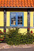 Blue window in the yellow house — Stock Photo