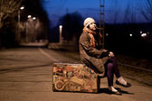 Girl in a coat sitting on a suitcase a railway station — Stock Photo
