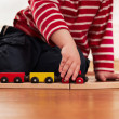 Child playing with toy wooden train — Stock Photo #10063622
