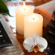 Stock Photo: Relaxing spa with candles orchids towels and stones