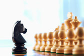 Chess black knight challenges white pawns — Stock Photo